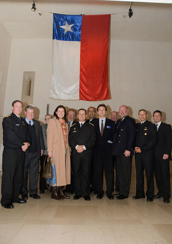Our guests from the Navy of Chile and the Royal Navy gather with museum representatives beneath the ensign from the Almirante Cochrane.