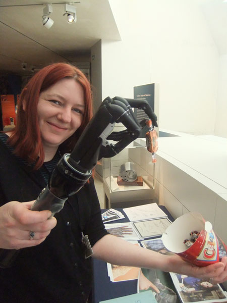 Curator Julie Orford with the i-limb hand on its torch 'forearm'. At the launch of the 26 Treasures project visitors could try it for themselves.