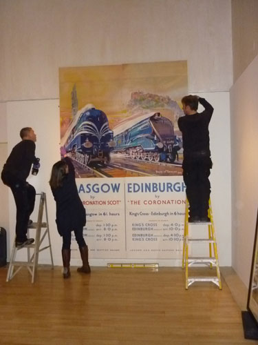 The finished poster being fixed to the wall in the gallery