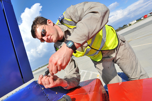 Blues engineer working on the tail of a Red Arrows Hawk jet © MOD Crown Copyright