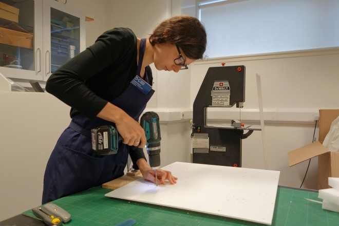 Assistant conservator Isabel Wagner drilling holes in correx sheets.