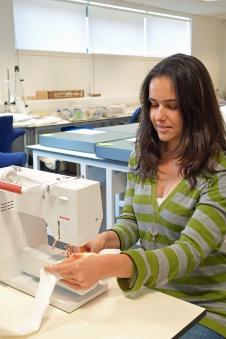 Artefact Conservation intern Beatriz Fonseca sewing Tyvek tubes.