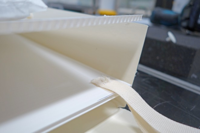 Cotton twill tape is inserted between the correx sheets and secured with plastic rivets.