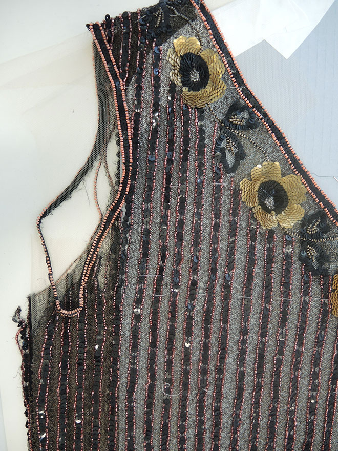 Detail of shattered and torn net at the underarms of the beaded dress