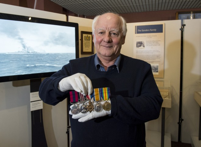 William Sanders holding his grandfather's medals