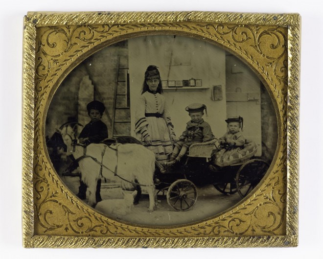 This tintype from the 1850s-60s shows a portrait of a woman with three children, taken in front of the itinerant photographer's van. From the Howarth-Loomes collection at National Museums Scotland.