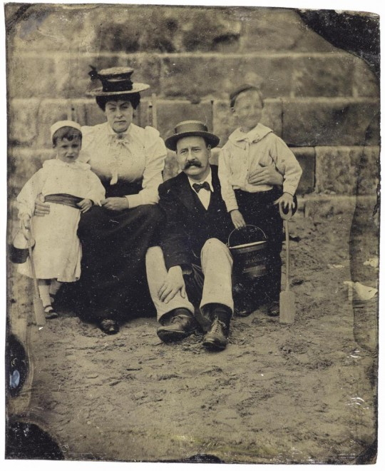 Tintype depicting a family group of parents and two young boys on a beach