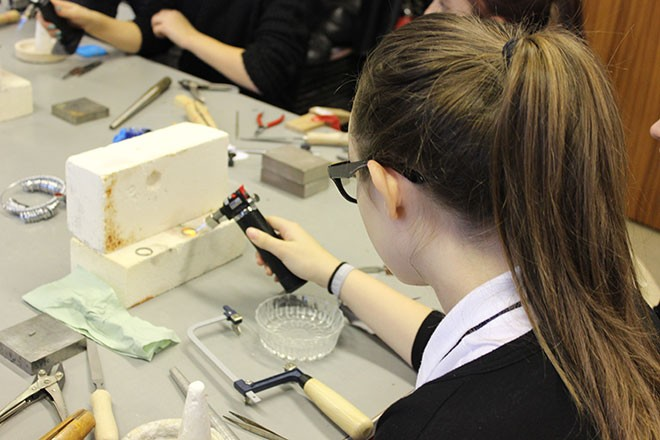 Pupils creating their own silver rings during a workshop at the school