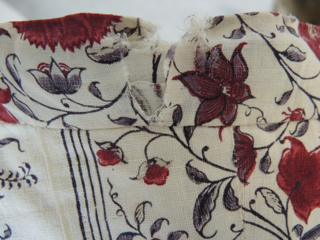 Split in the fabric on the back neck edge, before conservation