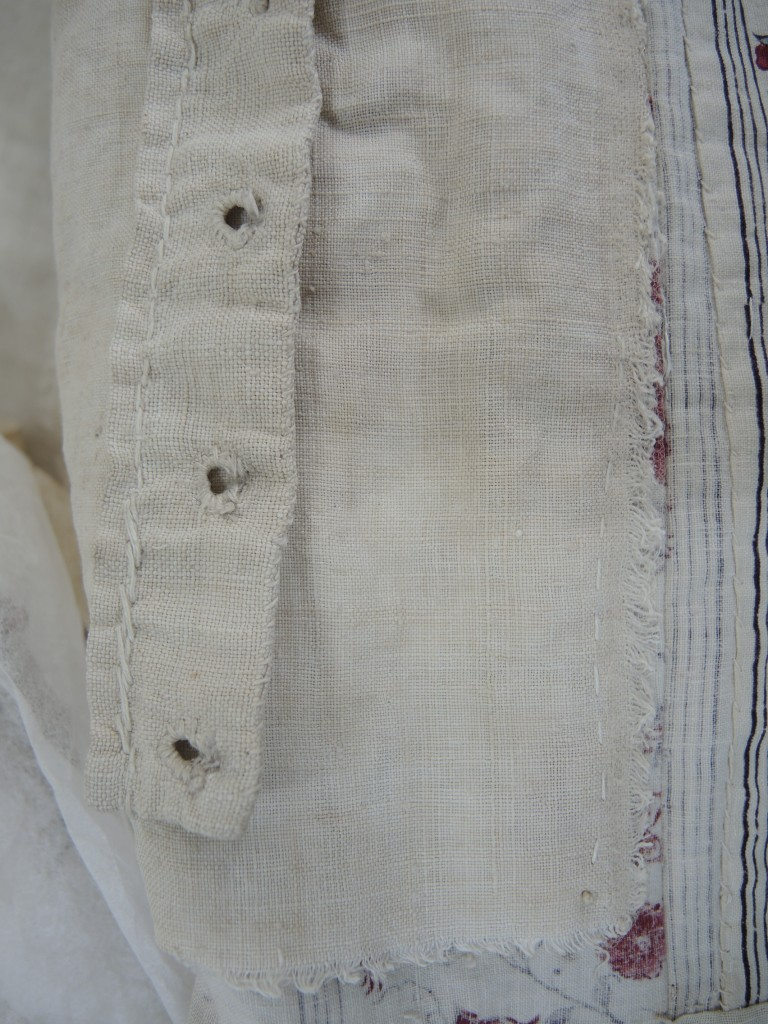 The detached edge of bodice lining encased in nylon net and re-stitched to the printed fabric, after conservation.