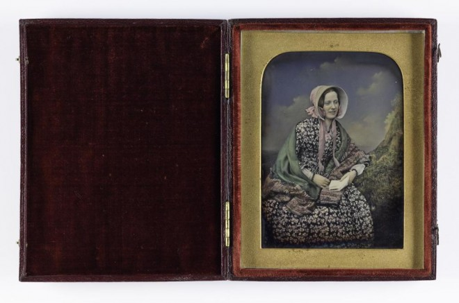 1/6 plate tinted daguerreotype, depicting a seated young woman wearing a bonnet, shawl and flower print dress, mounted and cased, by Beard's Photographic Institutions of London and Liverpool, 1852 - 1854