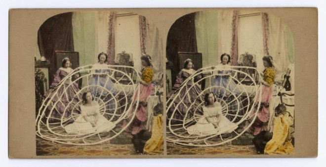 Coloured stereocard entitled 'Crinoline Made Useful' depicting a woman being dressed in a crinoline, by an unknown photographer. Features in Photography: A Victorian Sensation.