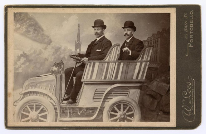 Cabinet portrait depicting two unidentified men seated in studio with car against the backdrop of Princes Street, Edinburgh and the Scott Monument, by W. Lees, Portobello, Edinburgh