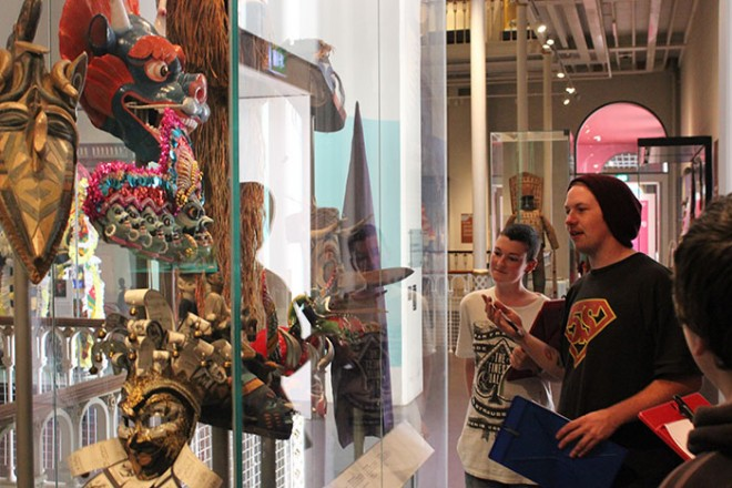 Young Demonstrator Liam pointing out some colourful masks in the World Cultures galleries