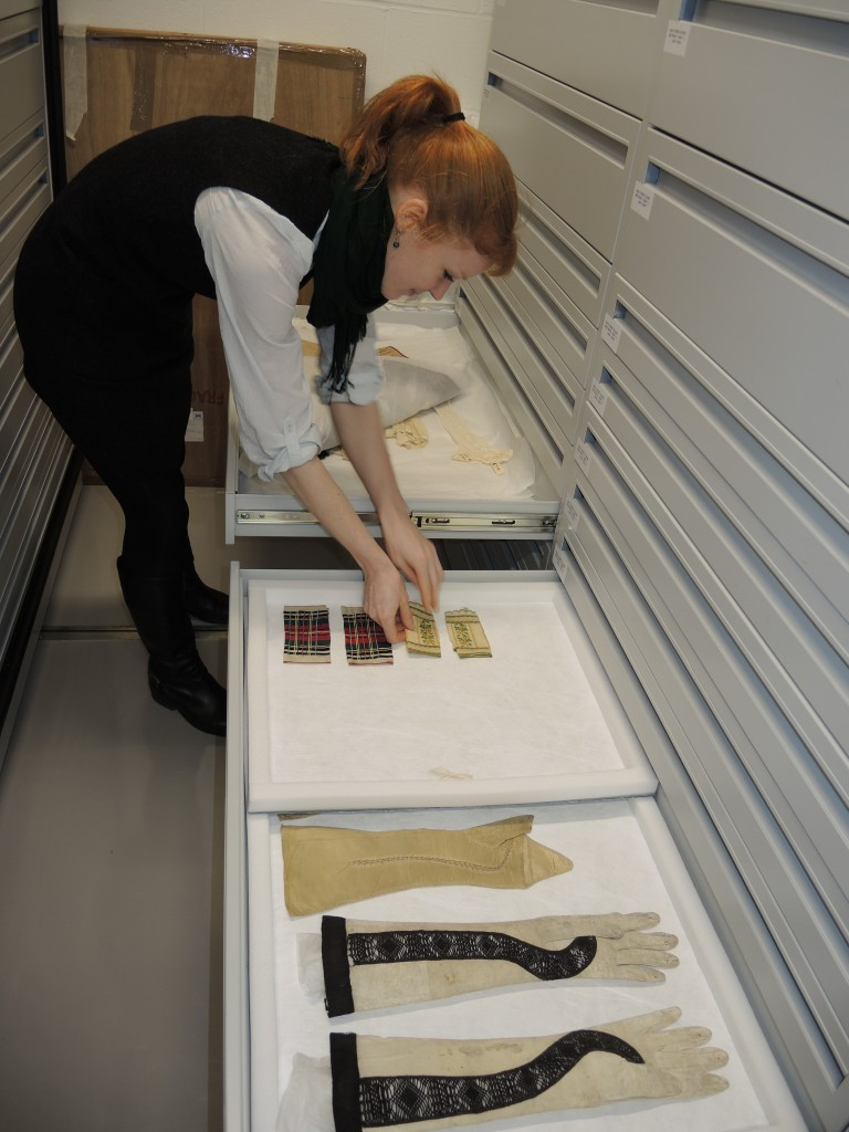 The gloves being moved by our Assistant Curator into the two sizes of trays which are stacked into the drawers.