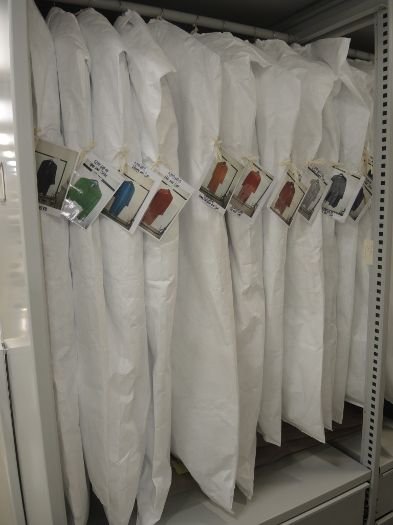 The Jean Muir garments on padded hangers, with Tyvek storage covers