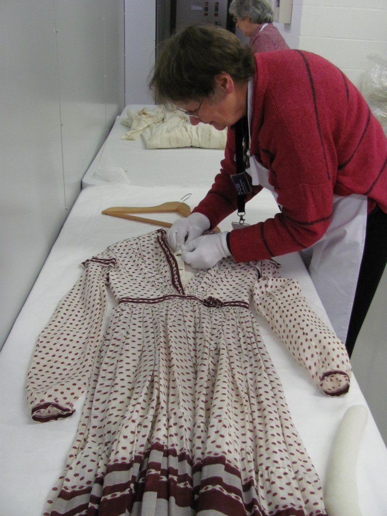 Volunteers working in the stores, removing the old hangers and selecting a new appropriately shaped padded hanger.