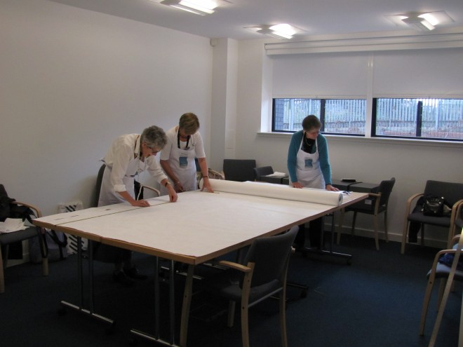 The team measuring and cutting the Tyvek for storage bags.