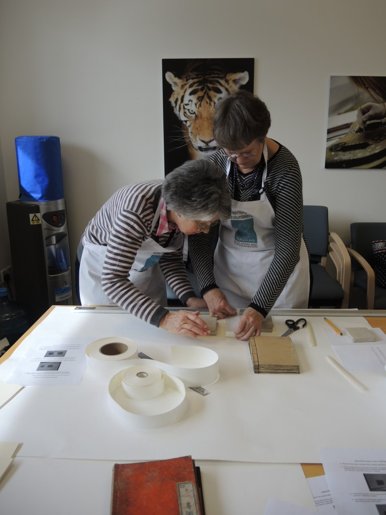 The team making the card support covers, and the curator opening one of the books which is supported by the new 'cover'.