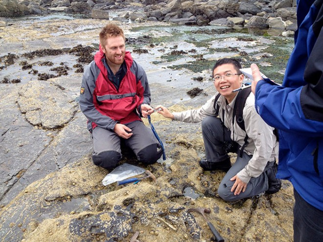 Tom explains the charms of fossil collecting in Skye to Li Chun