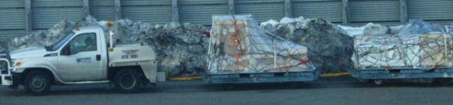 •The crates wrapped up and tied down, and being transported past dirty snowdrifts to the plane.