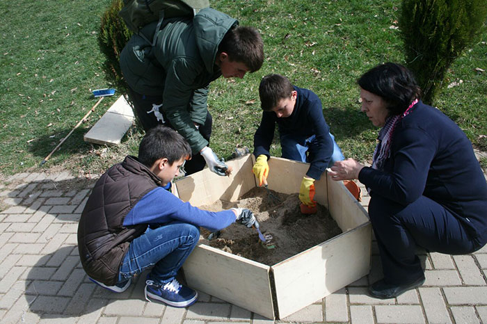 Director of the National Museum of Kosovo, Skender Boshtrakaj, shows how to assemble and use archaeological dig boxes that he designed.