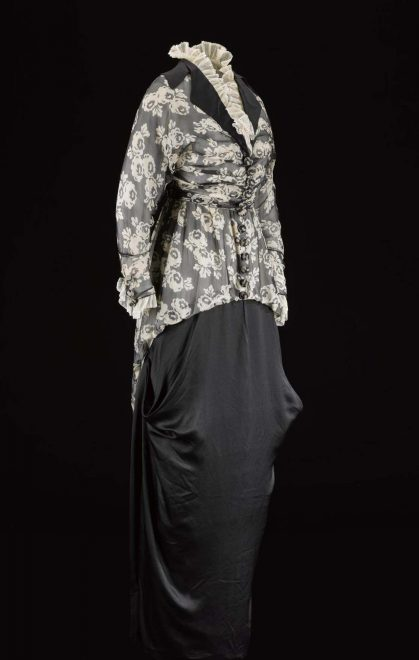 Woman's afternoon dress of silk chiffon printed with a patten of black with white flowers, and black silk satin and white silk net. The skirt is gathered towards the hem in a style known as the hobble skirt: British, c. 1913 - 1914