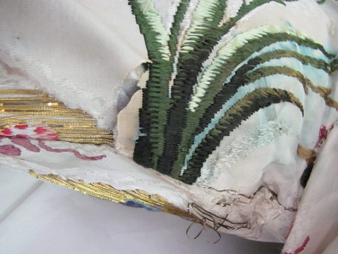 Detail of the split silk under the right arm before conservation.