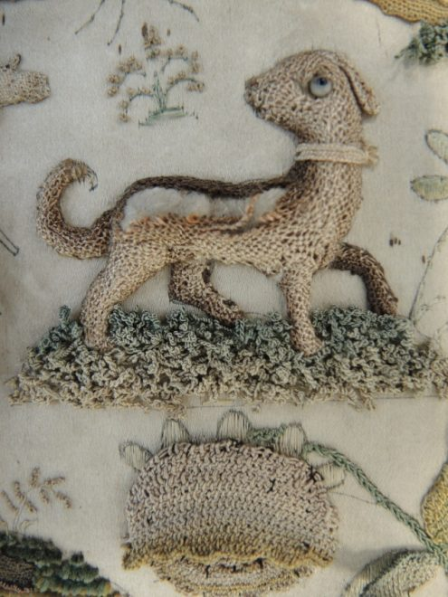 The dog with missing needle lace embroidery, exposing the padding underneath.