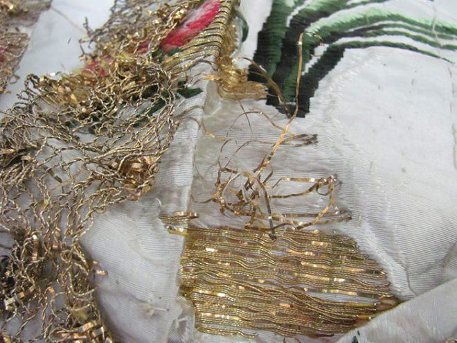 Broken and tangled gold thread on the front of the bodice. To the left of the image is the gold thread lace trim.