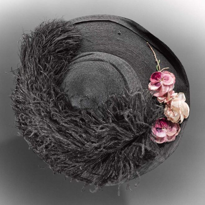 Women's hat, in black straw with a wide brim and shallow crown, brim trimmed with a black ostrich feather and cluster of pink silk and velvet flowers: Scottish, Glasgow, by Stewart & McDonald, c. 1900 - 1913.