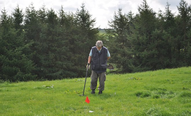 Hunting for clues with a metal-detector. The red flag marks precisely where a find comes from