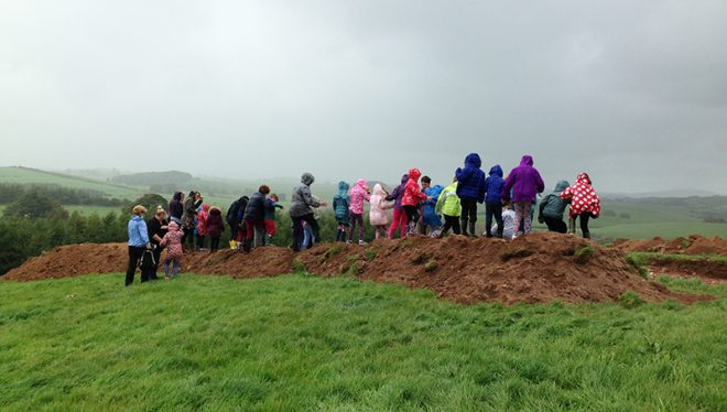 Schoolchildren from Castle Douglas Primary School helping us by sieving the topsoil, oblivious to the weather