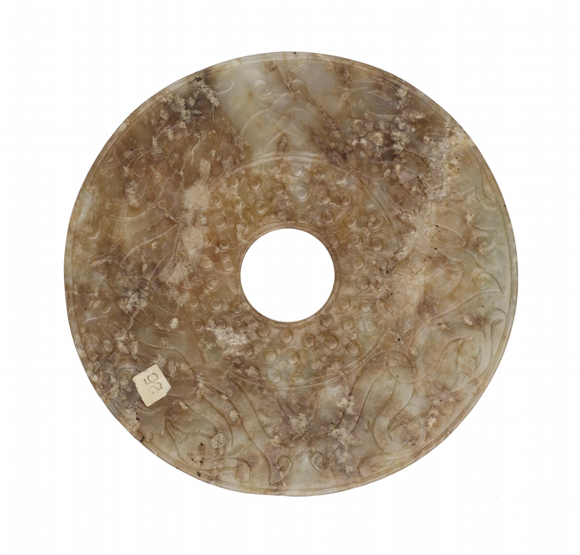 Bi disc of white jade carved on both sides in low relief with bird-headed scrolls interlacing in pairs and grain pattern: China, Han dynasty, 206 BC – 200 AD (A.1938.383).