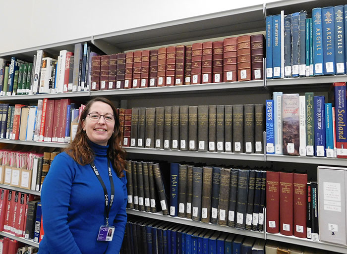 Julie Holder in the Research Library of National Museum of Scotland next to the Proceedings of the Society of Antiquaries of Scotland © Julie Holder
