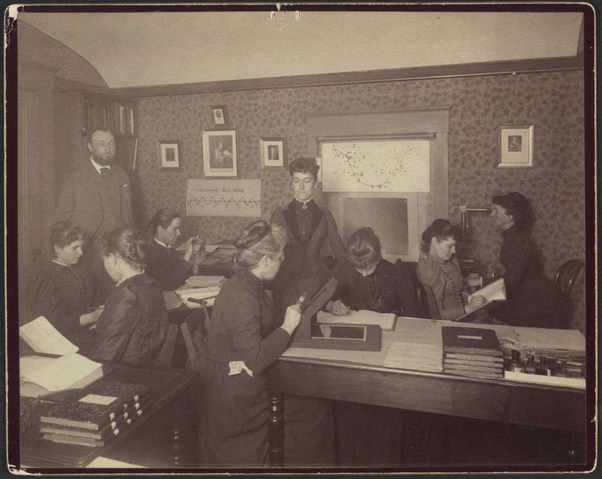 Williamina Fleming (standing) with some of the Observatory's women computers and the director Edward Pickering. The working conditions were less cramped than shown in this posed photo. Image: Observatory computer room and staff, 1891. HUV 1210 (9-4), olvwork289689. Harvard University Archives.