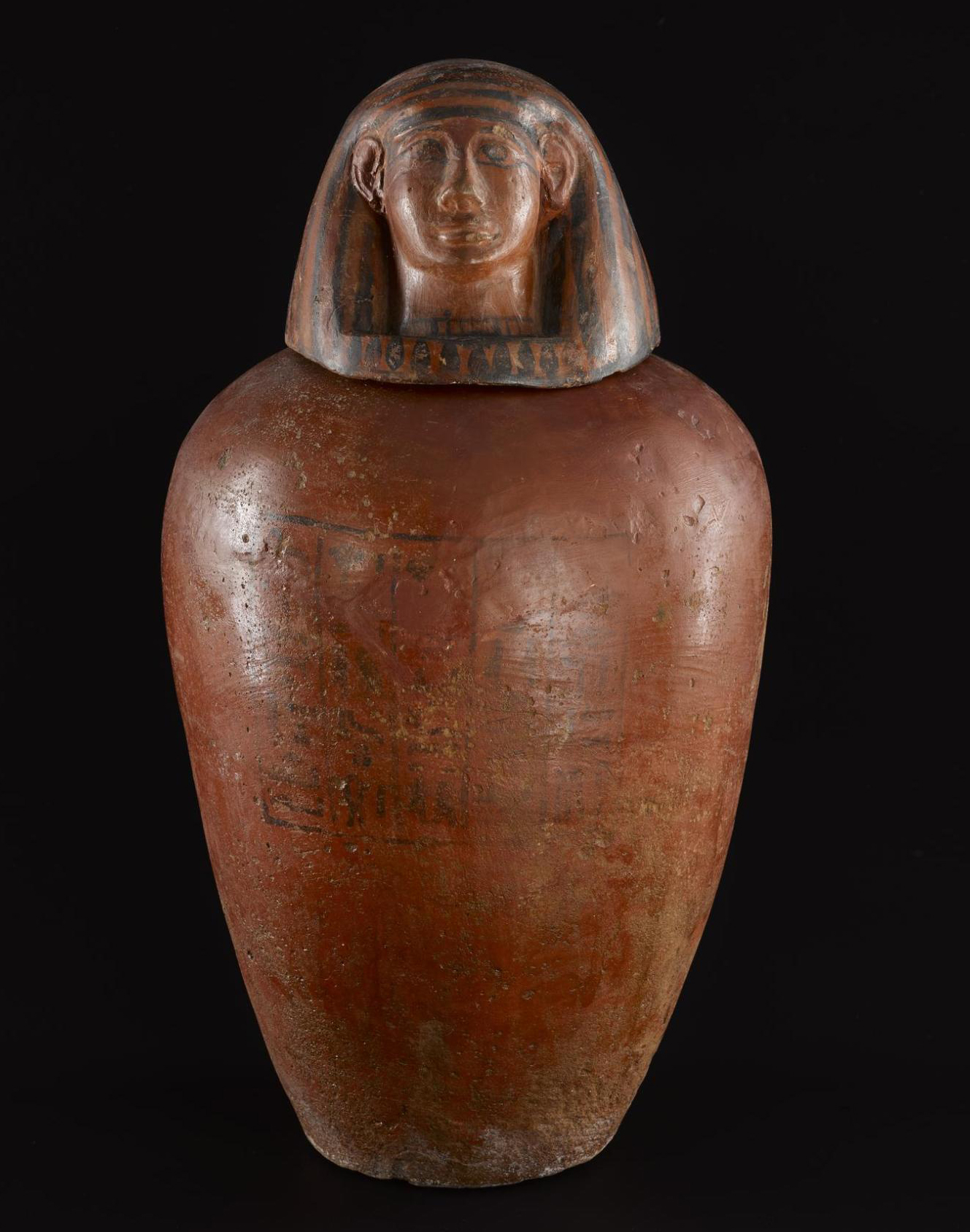 Canopic jar in dark red pottery with a human-headed lid representing one of the protective Sons of Horus, inscribed for the priest Amunmose: Sedment, Egypt, c.1479–1352BC.