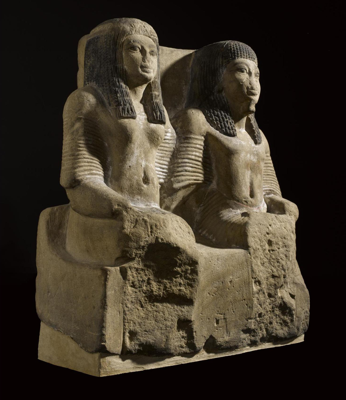 Sandstone statue of a Chief of the Police and his wife seated side by side, wearing long pleated robes and wigs: Sheikh Abd el-Qurna, Thebes, Egypt, c.1323–1279BC.