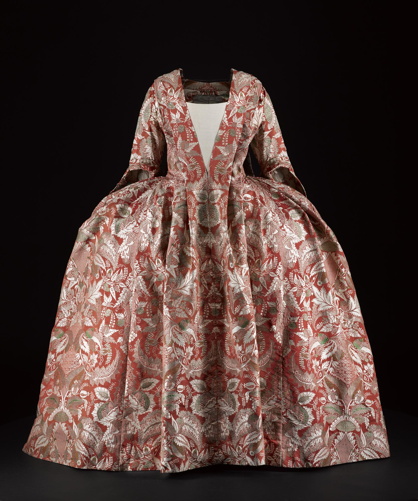 Woman's dress in red silk woven with a dense mirror repeat design of foliage in white, silver and green, in a sack (sacque) back or robe volante style, belonged to the Earls of Haddington, textile c. 1726-1728, dress c. 1740