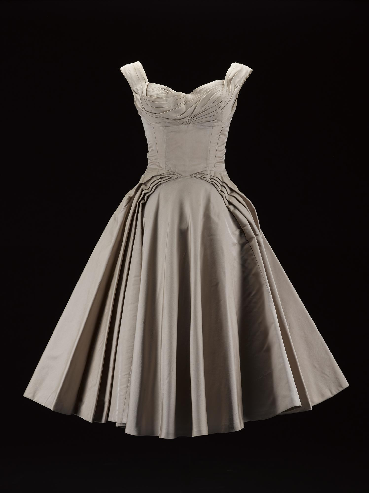 Woman's evening dress or ball gown, in pale beige silk taffeta, with a low sweetheart neckline with pleated detailing and wide shoulder straps, fitted, structured bodice with off-centre seams and padded bust and wide curving pleats to full stiffened skirt, three-quarter length, labelled in the centre back, the bodice of the dress is unlined, the skirt lined with stiffened paper: American, by Ceil Chapman, mid 1950s