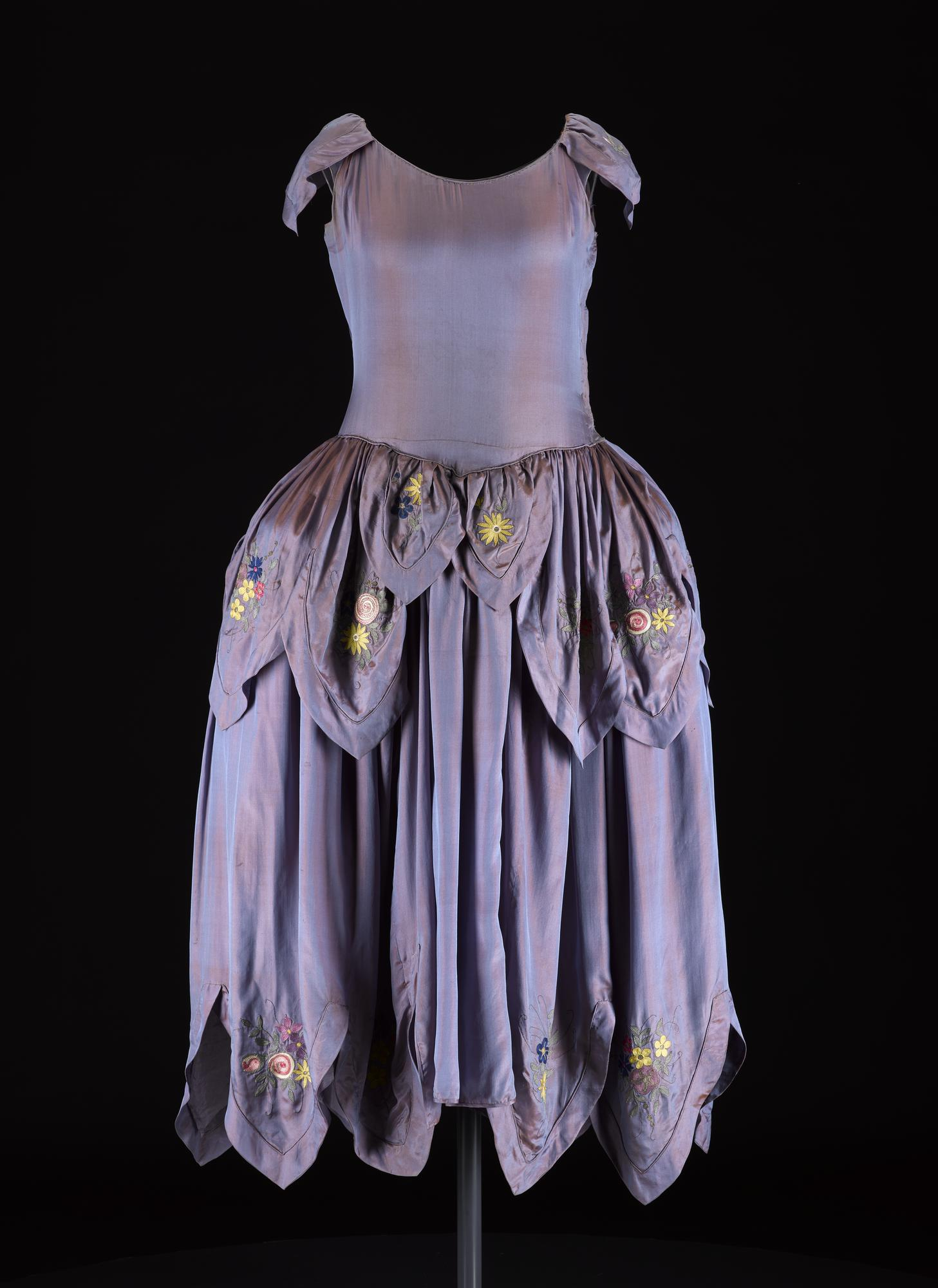Women's robe de style dress, in 'bleu de lanvin' irridescent (or shot) blue silk, with multicoloured floral embroidery at the hem and hips, featuring cap sleeves, a dropped waist with full pannier hips and a 'petal-shaped' hemline: France, Paris, designed by Lanvin, c. 1924.