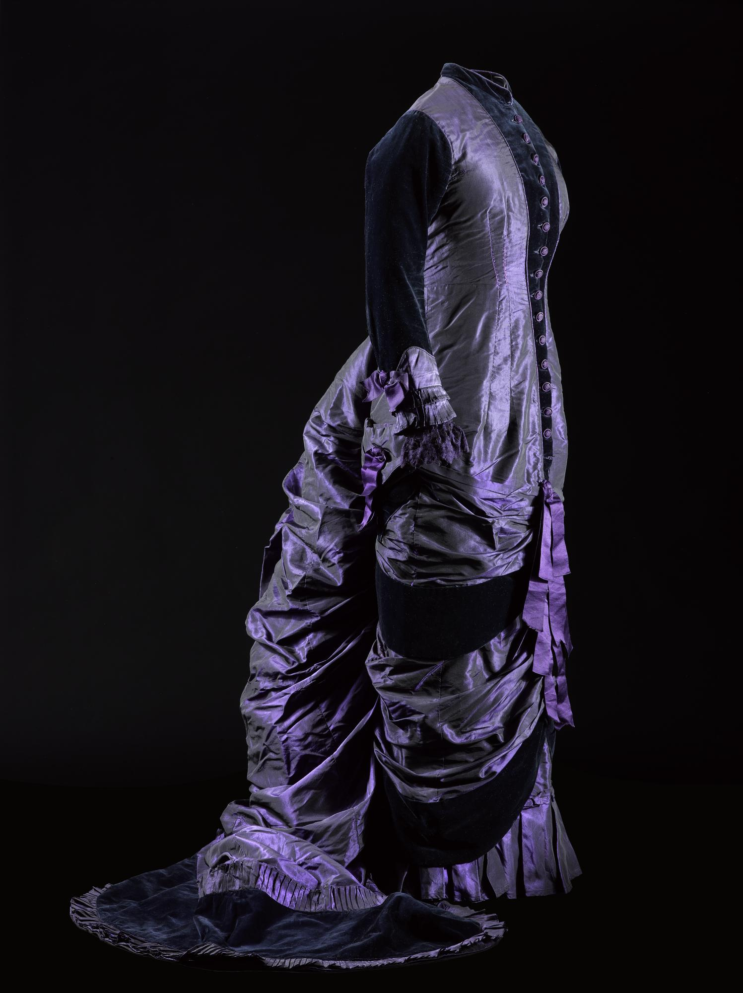 Woman's dress, in purple and black shot silk, trimmed with silk velvet, constructed with the princess line, with a high round neckline and centre front fastening trimmed with velvet, full-length velvet sleeves with shot silk cuffs trimmed with lace, narrow skirt with train falling in swags and cascade, with purple silk ribbons trimming the centre front, panels of velvet and velvet finishing the train: British, c. 1874 - 1879.