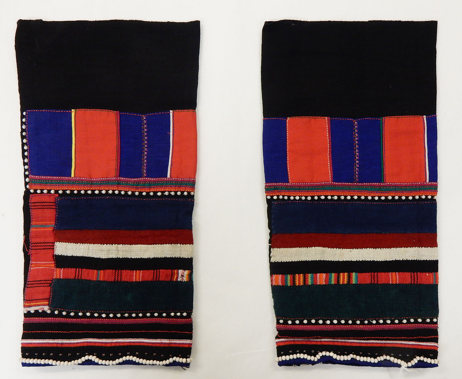 A pair of woman's black cotton leggings decorated with panels and stripes in cotton applique with white beads: May Wilson collection. Museum reference A.1984.594.