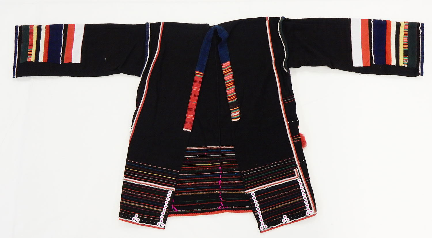Woman's jacket of black cotton decorated with stripes in red, white, blue and yellow applique, ornamented with buttons, tin studs, cowrie shells, coins, and monkey fur tufts: May Wilson collection. Museum reference A.1984.598.