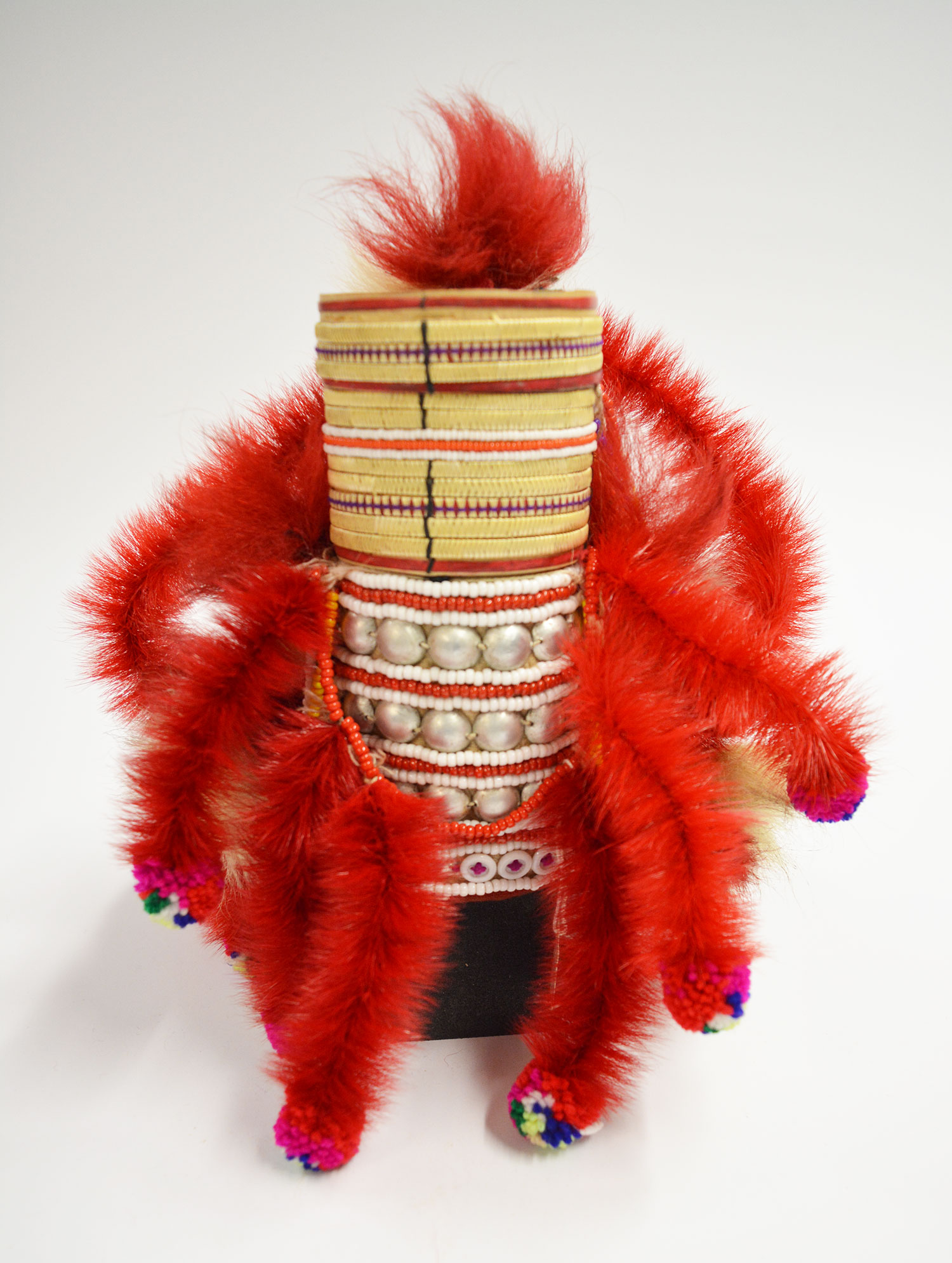 Woman's headdress or hat of cream cotton fabric stretched over a conical cane mount and decorated with strips of plaited straw, beads, tin studs, streamers of monkey fur and chicken feathers: May Wilson collection. Museum reference A.1984.599.