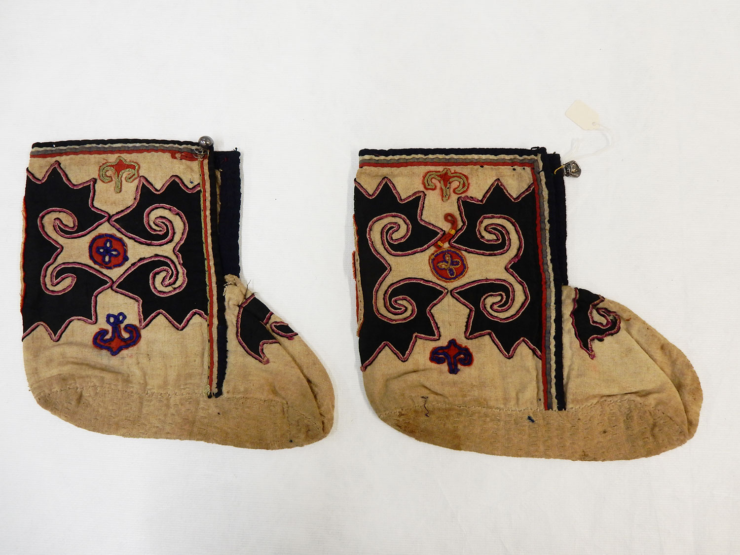 pair of unbleached white cotton boots, with applique decoration, and metal fastening: North Thailand, Yao people, also known as Mien, mid 20th century. Museum reference A.1988.220. A+B