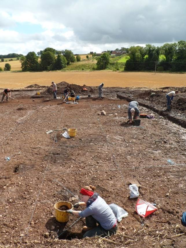 Digging the hoard site. The stub of one of the standing stones can be seen in the middle distance. The hoard was found towards the rear of the trench.