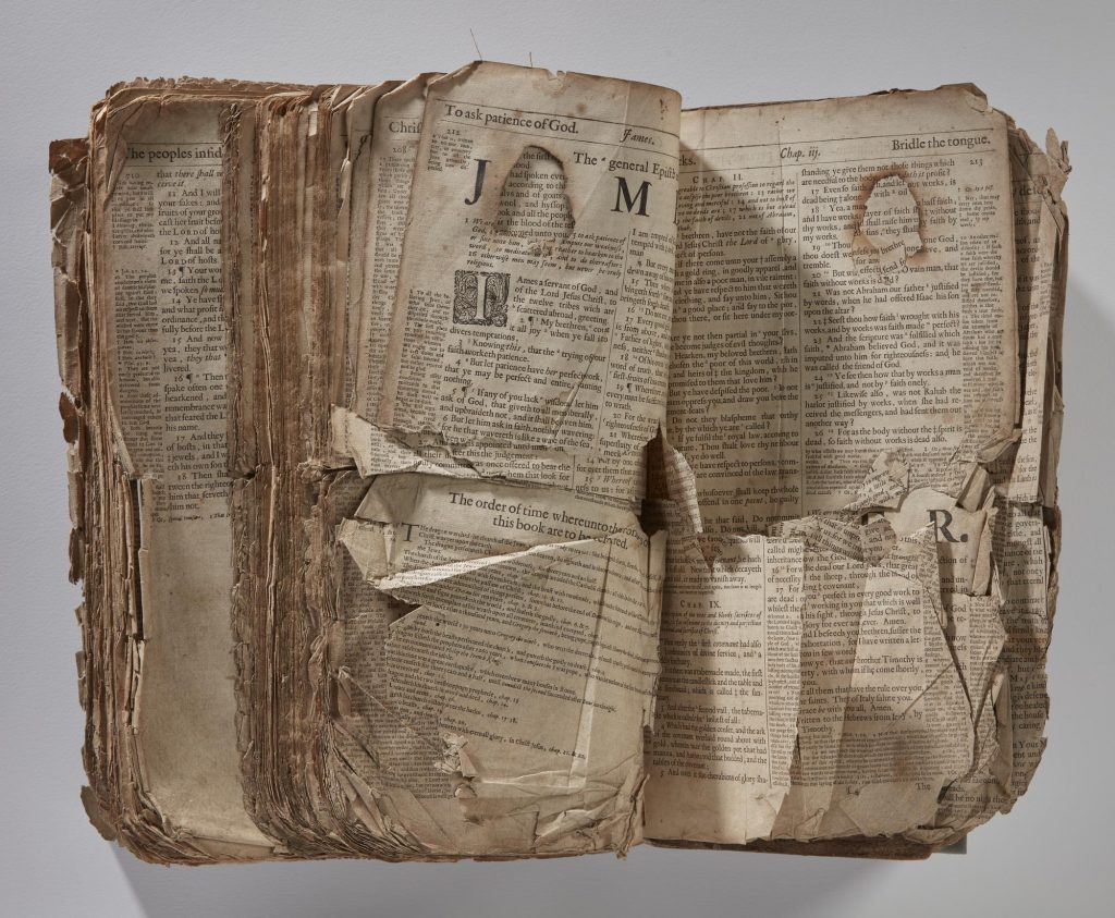 Fire-damaged areas and crumpled pages.