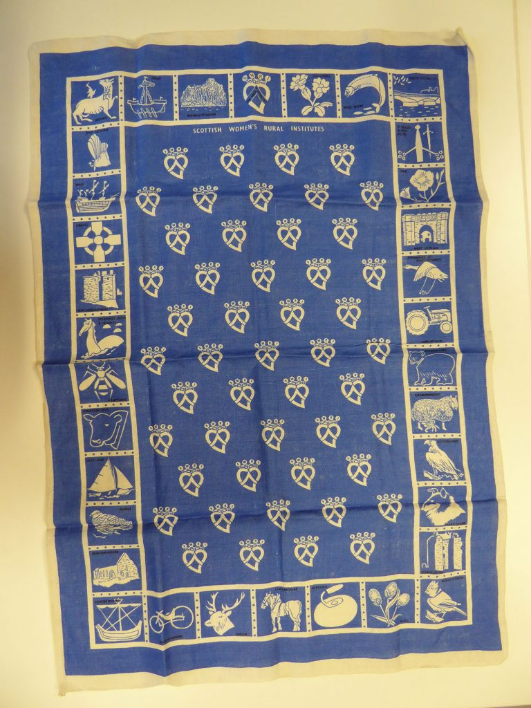 Linen tea towel, printed in blue with the emblems of 33 SWRI branches & the organisation's own emblem. c. 1974