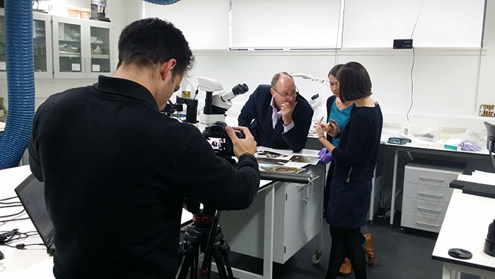 David Forsyth, Principal Curator of Renaissance and Early Modern History, Stefka Bargazova, Artefact Conservator and Helen Wyld, Senior Curator of Historic Textiles, examine the Jewel while Edinburgh Film Company's Luke Moodley sets up for the shoot.